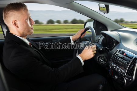 confident businessman driving car