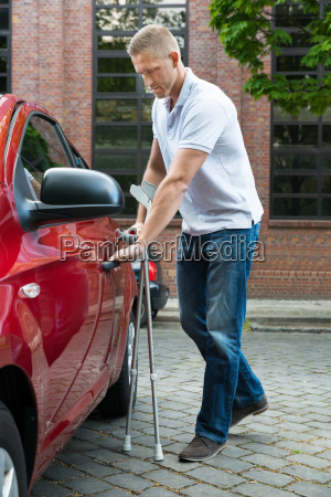 disabled man holding crutches opening door