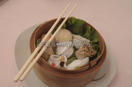 wontons in wooden bowl with sticks
