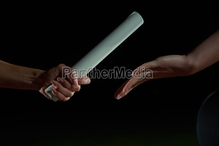 athletic runners passing baton in relay