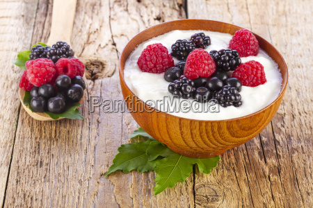 yogurt with wild berries in wooden