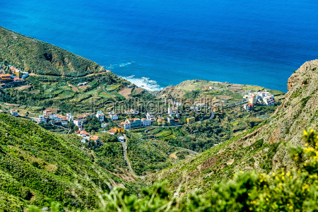 village in green valley near ocean
