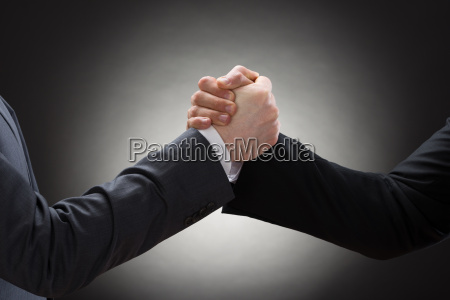 two businessman arm wrestling