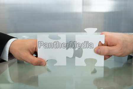 two businessman hands holding jigsaw puzzle