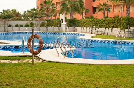 blue swimming pool and orange lifebelt