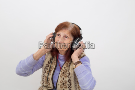 elderly lady listening music with headphones