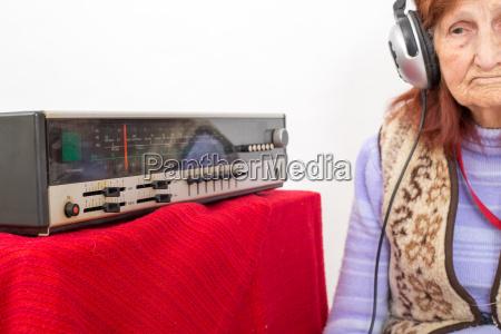 elderly lady listening to the radio