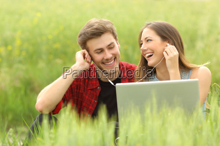 happy couple or friends sharing music