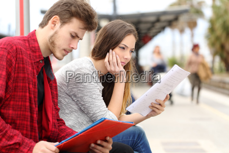 two students studying waiting transport in