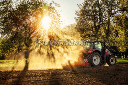 tractor plowing a field at sunset