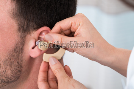 hands inserting a hearing aid into