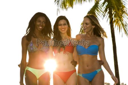 three women in bikini walking back