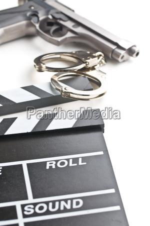 movie clapper and gun with handcuffs