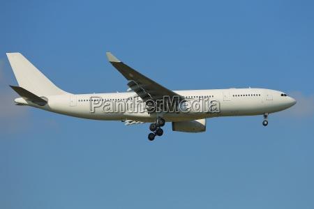 plane landing against clear blue sky
