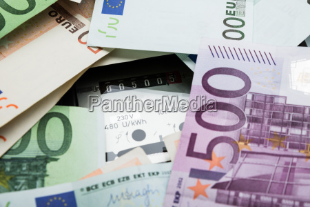 euro banknotes over electricity meter