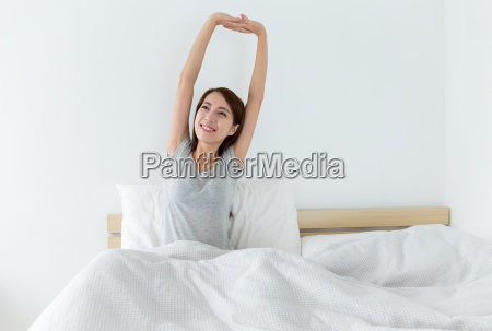 young woman waking up happily after