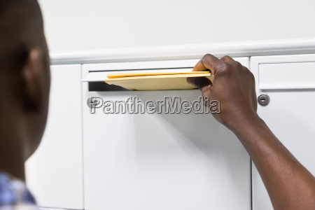 person hands putting envelope in postbox
