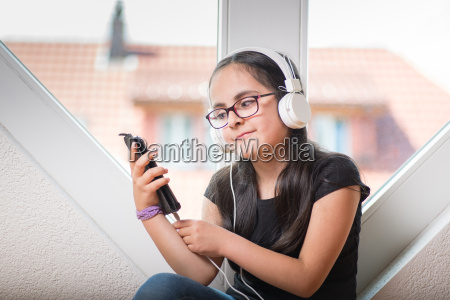 cute girl with glasses listening to