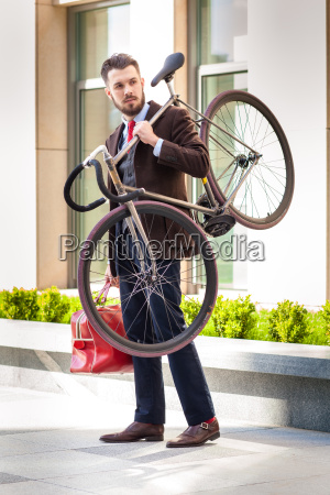 handsome businessman carrying his bicycle in
