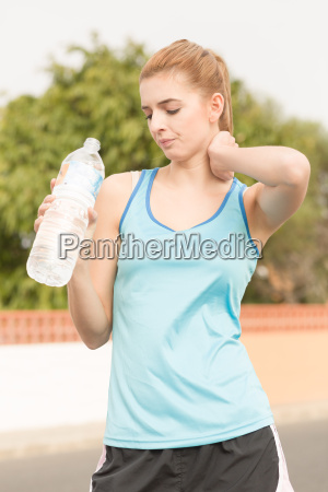 young woman doing sports and drinking