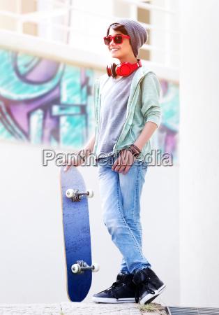 cute teen boy with skateboard