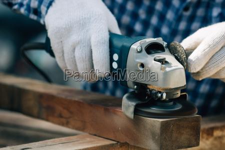 close up working carpenter shaving wood