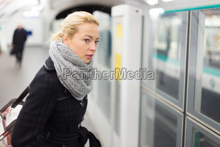 young woman on platform of metro