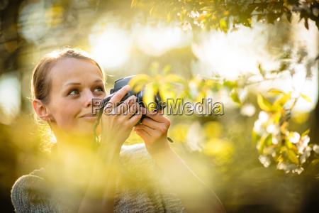 pretty female amateur photographer taking photos