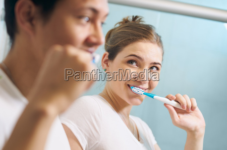 couple cleans teeth man and woman