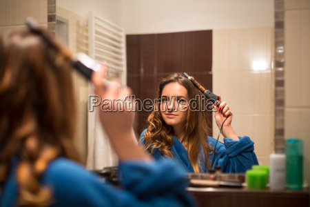 pretty young woman curling her hair