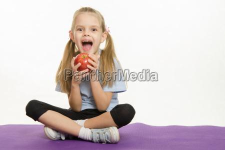 cheerful girl athlete eating apple