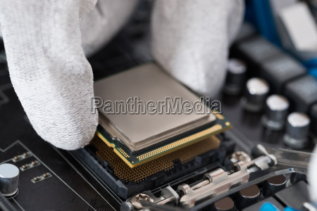 person installing central processor in motherboard