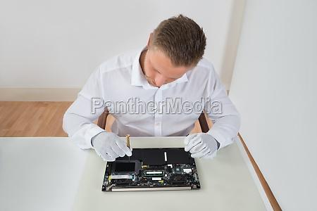 male worker repairing laptop