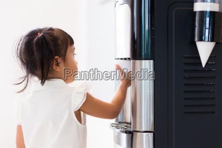 baby girl using the water machine