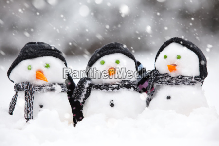 three cute snowmen in a snow