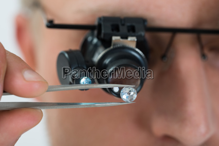 person looking at diamond with magnifying