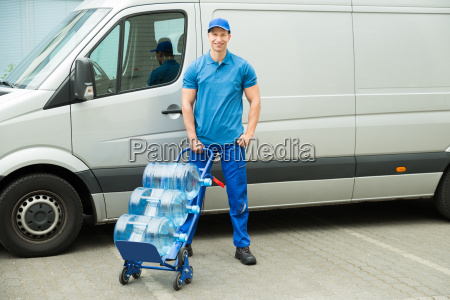 delivery man holding trolley with water