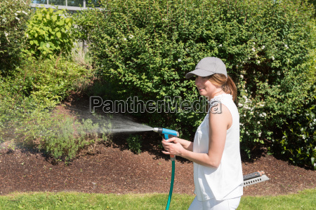 attractive young woman watering the plants