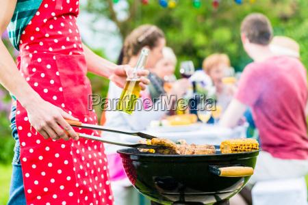 mann bedient den grill auf gartenparty