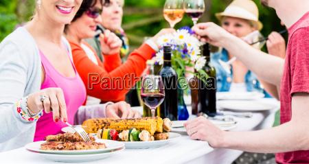 maenner und frauen feiern auf gartenparty