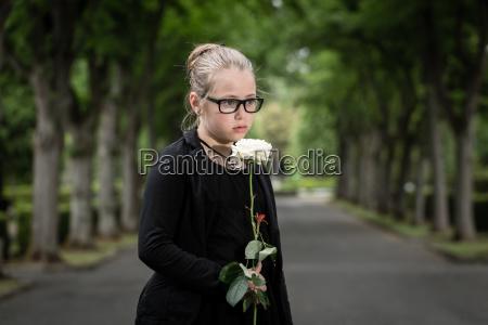 maedchen mit weisser rose trauert auf
