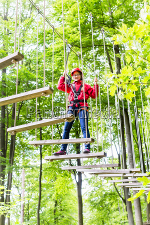 kind klettert im hochseilgarten und erreicht