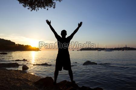 man saluting sun at sea
