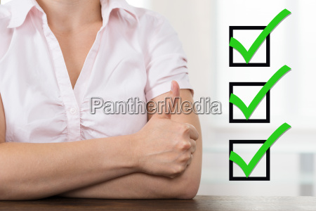 businesswoman with checklist showing thumb up