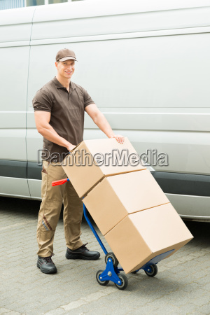delivery man holding trolley with cardboard