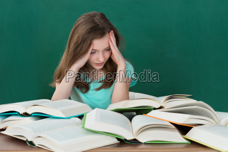 girl at desk with many books