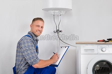 plumber writing meter reading on clipboard