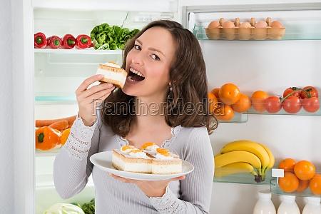 woman eating slice of cake