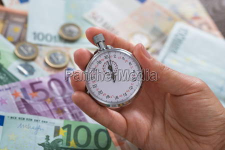 person hands with stopwatch over money