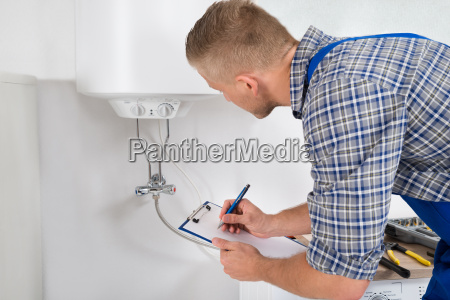 plumber with clipboard in front of